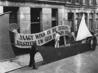 1977-3522 Bij het stadhuis wordt gewerkt aan een model van een zeilschip met het opschrift: Jaagt wind in de zeilen: ...