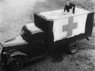1977-3631 Vrachtauto wordt voorzien van de Rode Kruisvlag.