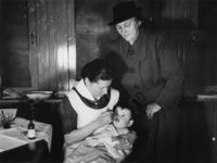 1977-3680 Een verpleegkundige van de GGD (Gemeentelijke Geneeskundige Dienst) verstrekt vitamine D aan een peuter.