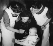 1977-3681 Verpleegkundigen van de GGD (Gemeentelijke Geneeskundige Dienst) verstrekken vitamine D aan een baby.