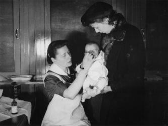 1977-3682 Tijdens de bezetting in de Tweede Wereldoorlog. Openbare diensten. Verpleegkundige van de GGD (Gemeentelijke ...
