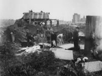 1977-3687 Op de Westzeedijk wordt een Duitse post voor afweergeschut gesloopt door mensen die op zoek zijn naar ...