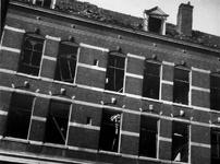 1977-3696 Gezicht in de Lombokstraat met vernielingen aan vensters en dakpartij van huizen als gevolg van de ...