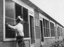 1977-3725 Glazenzetters aan het werk bij noodwoningen in het Brabants Dorp..
