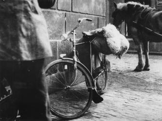 1977-3786 Een zak wol op de bagagedrager van een fiets. Op de achtergrond een bespannen paard.