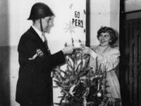 1977-3803 Een functionaris van een blokploeg van de luchtbeschermingsdienst (LBD) in uniform bij een kerstboom.