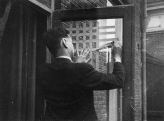 1977-3806 Ter bescherming van een ruit van een deur wordt het glas met stroken papier beplakt.