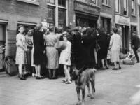 1977-3809 Mensen staan in de Vierambachtsstraat in de rij bij aardappelhandel Jac. J. v.d. Veer. Op de achtergrond: ...