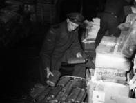 1977-3952 Een beambte van de douane controleert hulpgoederen (kruiken en en sigaretten), bestemd voor de slachtoffers ...