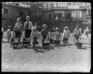 2004-1999-02 Kinderen spelen met kruiwagens in het zand op een zomerse dag. Op de achtergrond woningen.