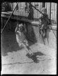 2004-1999-05 Moeders kijken vanachter een hek naar spelende en schommelende kinderen in het zand. Onbekende locatie.