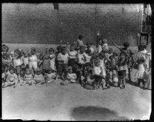 2004-1999-06 Groep jonge kinderen in het zand van een speelterrein op een zonnige dag. Onbekende locatie.