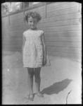 2004-1999-08 Portret van een meisje in zomerjurk in het zand van een speelterrein op een zonnige dag. Onbekende locatie.