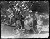 20041999-03 Kinderen spelen in het zand op een zomerse dag. Moeders zitten op een bankje. Onbekende locatie.