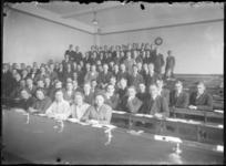 2007-2543-05 Groepsportret in een collegezaal met studenten en docenten van de Nederlandsche Handels-Hoogeschool aan de ...