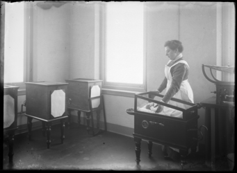 2007-2559-07 De Rijkskweekschool voor vroedvrouwen aan de Henegouwerlaan. Een interieurfoto van een zaal met enkele ...