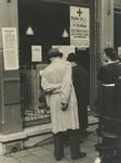 XXXIII-650-03 Voor de Rode Kruiswinkel no. 52, waar gratis levensmiddelen wordt uitgereikt. Met op de gevel en etalage ...