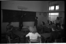 1009-01 Docent en kinderen in een klaslokaal van een school van de Ammanstichting. De stichting verzorgde onderwijs ...