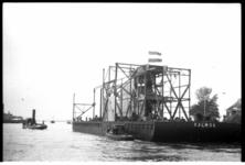 1017-01 Zeetinbaggermolen Kalmoa wordt begeleid door sleepboten bij het vertrek naar Indië, ter hoogte van Kinderdijk.