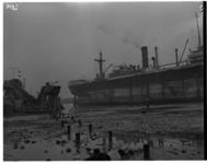 1023-04 Bij Hoek van Holland vastgelopen schip Captitaine G. Lacoley. Links een baggeraar.