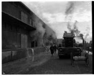 1048-06 Brandweerwagen en brandweermannen bij een brand bij N.V. Katoenveem aan de Keilestraat.