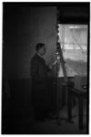 1078-01 Een spreker staat bij een microfoon voor een radio-uitzending. Uit een serie over activiteiten rond de Tweede ...