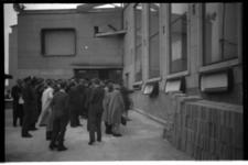 1078-02 Belangstellenden bekijken de uitslagen van de Tweede Kamerverkiezingen die op ramen van het gebouw van het ...
