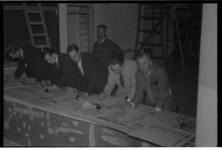 1078-05 Mannen schrijven op posters de uitslagen van de Tweede Kamerverkiezingen. Op de posters staat de kop 'stand der ...