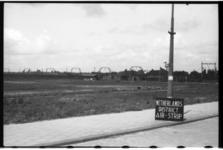 368-02 Bord met opschrift 'Netherlands district air-strip' staat tegen een lantarenpaal. In de omgeving van Gordelweg ...