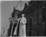 69 Mevrouw Grimberg dirigeert tijdens een zangfeest op de Coolsingel voor het stadhuis.
