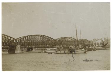 1981-750 Spoorbrug over de Nieuwe Maas met zicht op de Maaskade en enkele schepen, uit het oosten.