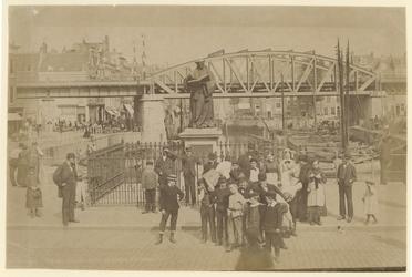 1989-111 Standbeeld van Erasmus op de Grote Markt met op de achtergrond de spoorlijn. Voor het standbeeld poseren ...