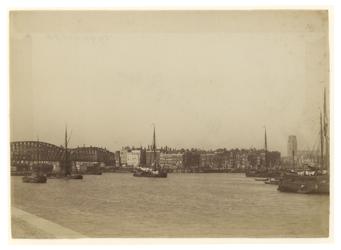 1990-1276 Nieuwe Maas voor het Bolwerk en de spoorbrug vanaf de Maaskade. In de Maas zijn schepen te zien.