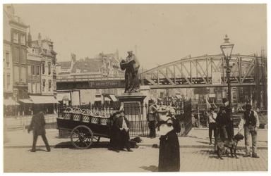 IV-18-3 Grote Markt met op de achtergrond de spoorbrug. Op de voorgrond enkele mensen op straat bij het standbeeld van ...
