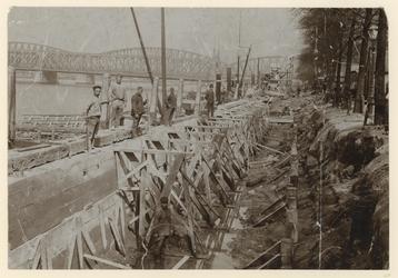 IX-1851-01 Maaskade uit het Westen met in de verte de Maasbrug. Op de voorgrond werkmannen aan het werk.