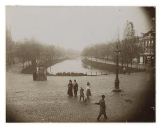 IX-2169-01 Zicht op de Noordsingel met aan weerskanten huizen. Op de voorgrond lopen een man en zijn vrouw en ...