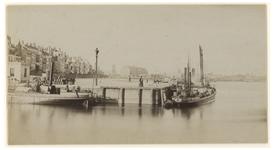 IX-2202-01 Zicht op de Oosterhaven met een enkel scheepje die aangemeerd is, de Oosterkade en de Maasboulevard.