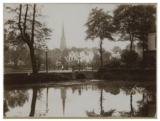 IX-2924 Zicht op de vijver in Park Honingen en uitzicht op de Slotlaan. Op de achtergrond is een kerktoren te zien.