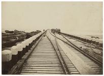 RI-93-2 Zicht op een spoorlijn. Aan de linkerkant liggen scheepjes en op de spoorlijn staat een wagon met stenen daarop.