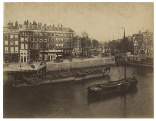VII-384 Zicht op de Mosseltrap en de Roobrug bij de Nieuwehaven. In de haven liggen enkele schepen.