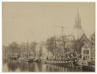 VII-465 Zicht op de Scheepmakershaven met zeilschepen aan de kant van het water. Aan de rechterkant is de toren van de ...