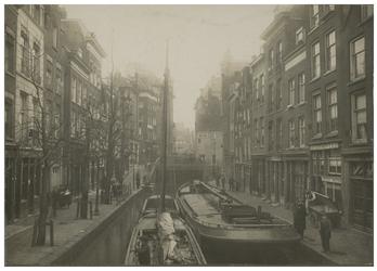 VIII-96a Ingang van de sluis van de Vlasmarkt aan de zijde van de Delftsevaart. In het midden van het water een paar ...