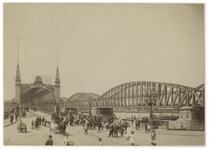 X-14 Zicht op de Maasbruggen. Op de voorgrond staat een menigte van mensen op straat. Aan de rechterkant is de ...