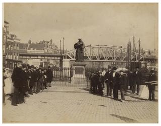 XXVI-10 Groep mensen keurig opgesteld op de Grote Markt bij het standbeeld van Desiderius Erasmus. Op de achtergrond is ...