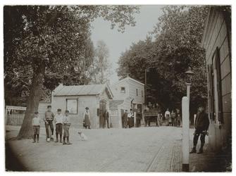 XXXI-169 De Straatweg met een tolhuis op de hoek van de Kleiweg, uit het zuidwesten. Op straat verschillende mensen, ...