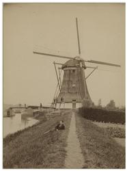 XXXI-449 De laatste watermolen aan de Boezem, nabij Overschie, uit het zuidoosten. Op de voorgrond in het gras ligt een ...