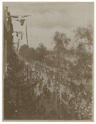 XXXIII-155-2 Stoet met praalwagens met paarden ervoor met op de voorgrond aan weerszijden een menigte van toeschouwers ...