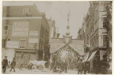 XXXIII-161-1-a Mensen op straat bij de Korte Hoogstraat, waarboven een sierboog is gespannen ter ere van Koningin ...