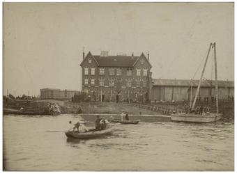 XXXIII-162 Instorting van de Wilhelminakade. Aan de linkerkant in het water zitten drie mannen in een bootje, verderop ...