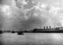 1970-1275 De Nieuwe Maas met een passagiersschip aan de Wilhelminakade bij het gebouw van de Holland Amerika Lijn. Op ...